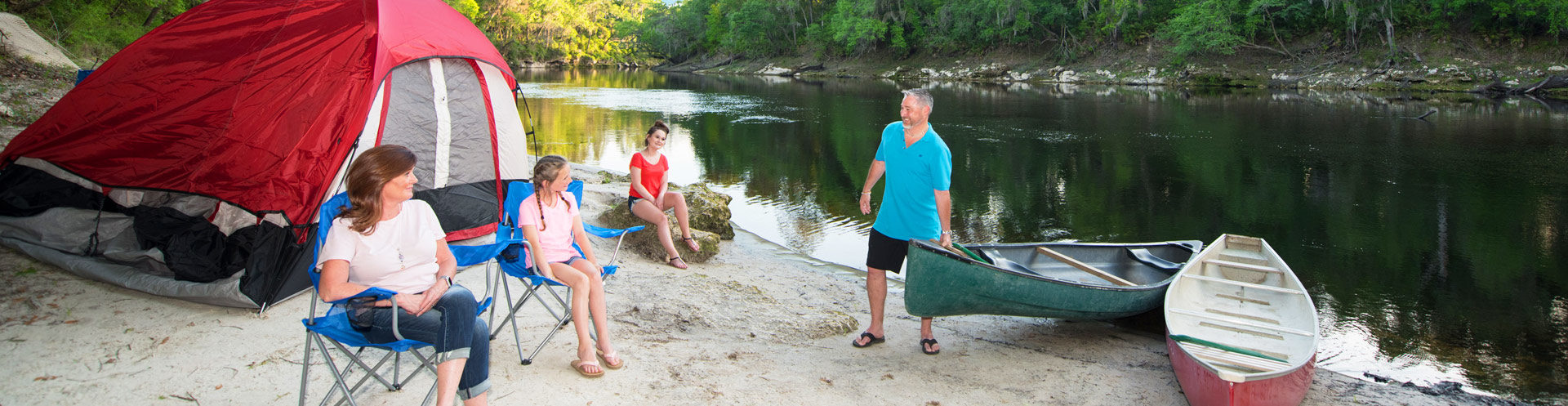 family at campground in suwannee with tent and kayaks