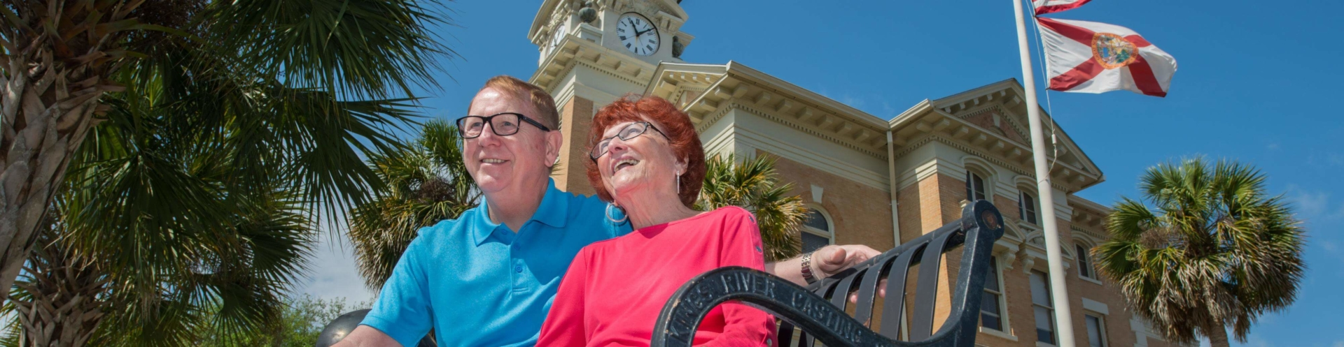 Couple sitting on bench in front of Suwannee County Courthouse