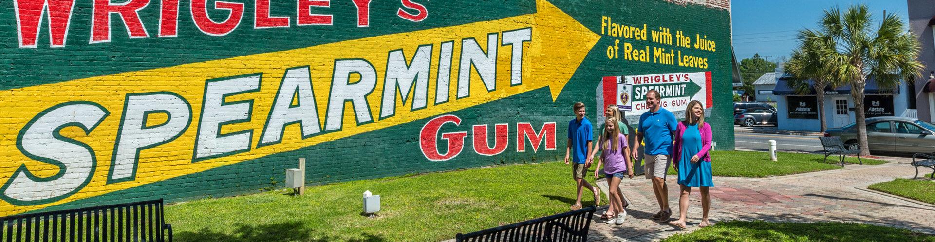 family walking by wrigleys spearmint gum mural in suwannee