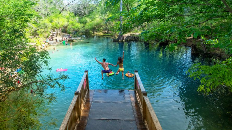 man and woman jumping into royal springs from dive platform