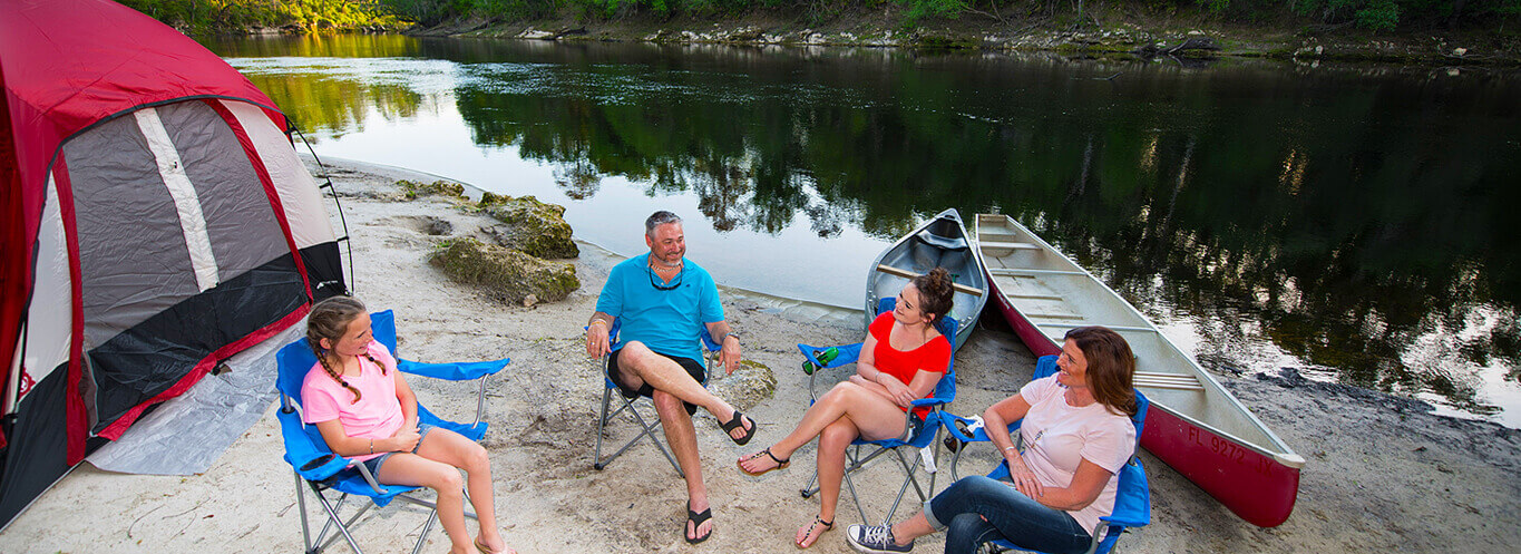 campers sitting in chairs by river in suwannee campground