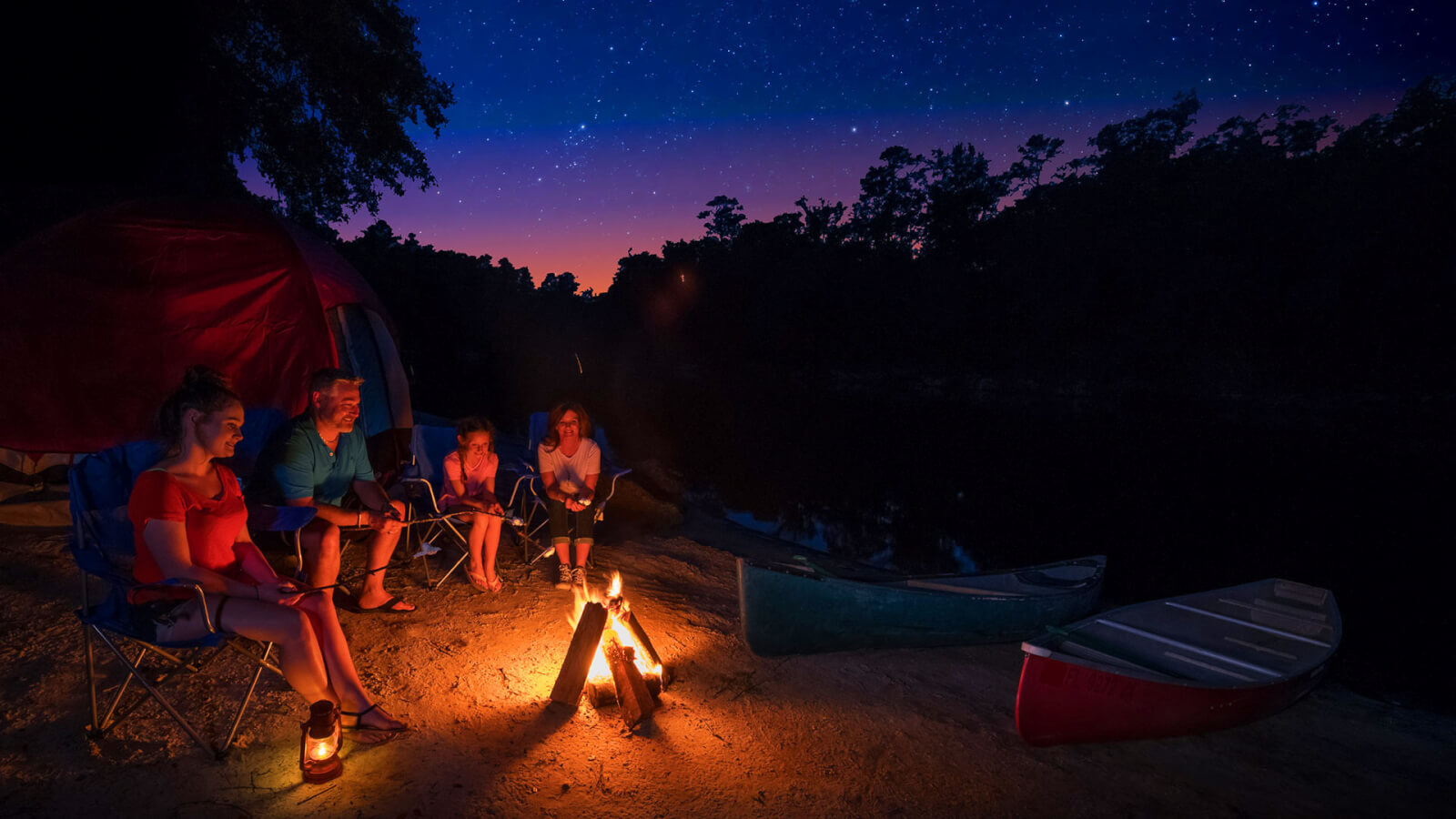 family roasting marshmallows at night in Suwannee campground