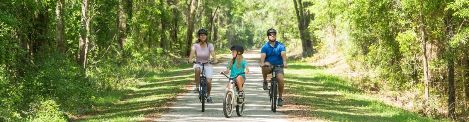 Family riding bikes on a path