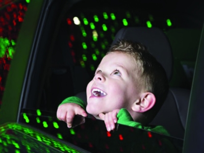 Child looks out a car window at Christmas lights